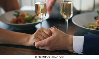 Close-up shot of male hand holding female hand on table with...