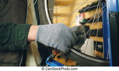 Close-up shot of male hand in greasy glove rotating broken bicycle wheel and straightening bent spokes with tools. Work, people and profession concept.