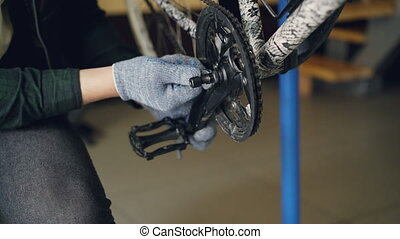 Close-up shot of male hands in protective gloves repairing...