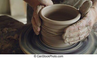 Close-up shot of male hands working with clay on spinning...