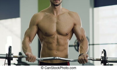 Close up shot of male torso during pumping arms muscle...