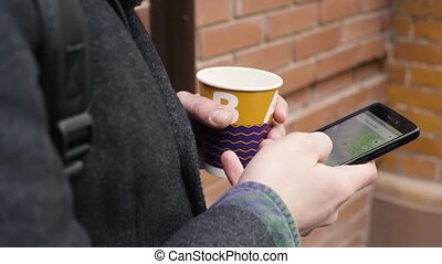 Close-up shot of man drinks coffee and use smartphone standing near a house in the alley