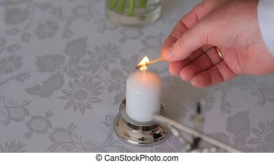 Close-up shot of Man's hands are lighting the candle. Close shot.