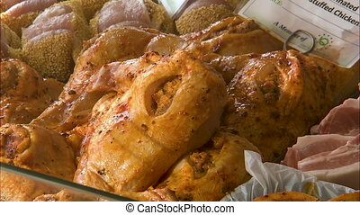 Close up shot of marinated and stuffed chicken on display in...