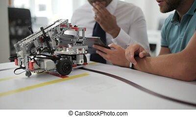 Close up shot of men discussing robotic devise in studio