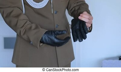 Close-up shot of Military groom is putting on leather gloves.