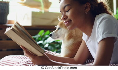 Close-up shot of mixed race girl dog owner reading book...