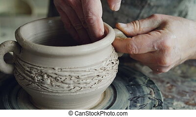 Close-up shot of muddy male potter's hands shaping and fixing ears of ceramic bowl. Nimble craftsman is forming clay professionally creating beautiful clayware.