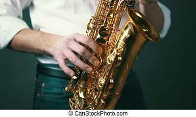 Close up shot of musician playing saxophone in studio. Real time.
