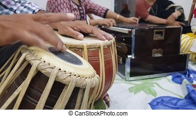 close up shot of pair of hands playing indian classical music instrument tabla and playing of harmonium in background.
