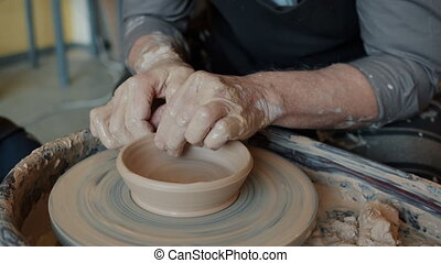 Close-up shot of potter's hands smoothing molded pot on ...