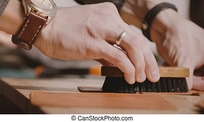 Close-up shot of professional male artisan hands polishing...