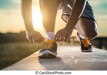 Close up shot of runner's shoes - Man tying jogging shoes. A...