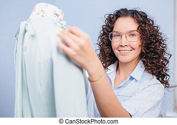 close up shot of seamstress adjusting dress on dummy at tailor shop