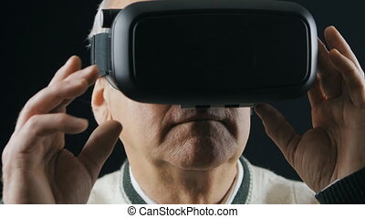 Close-up shot of senior man getting experience in using VR-headset in dark room