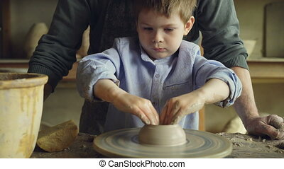 Close-up shot of serious little boy making clay figure on throwing wheel while his grandfather experienced sculptor is standing near worktable and watching.