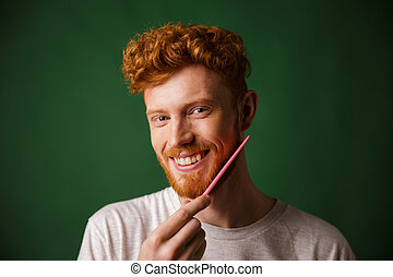 Close-up shot of smiling readhead man, combing his beard with pink comb