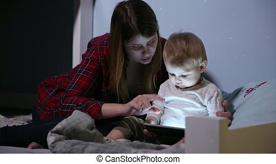 Close-up shot of son and mother in bed playing game on touch pad. Bedtime entertainment.
