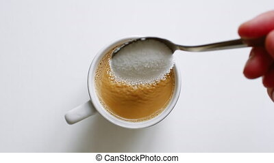 Close up shot of sugar being poured into coffee