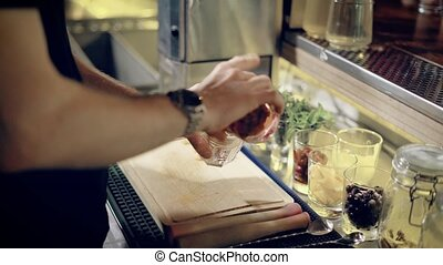 close up shot of the hands of the bartender, who mixes the...