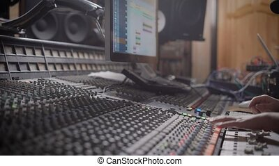 close up shot of the person hand, who is working on creating an electro melody in the sound recording studio, the man changes the tempo of the composition