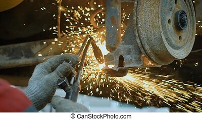 close up shot of the tire changer hands, who uses the Bulgarian in order to utilize the details of a rusty machine, sparks fly from the instrument