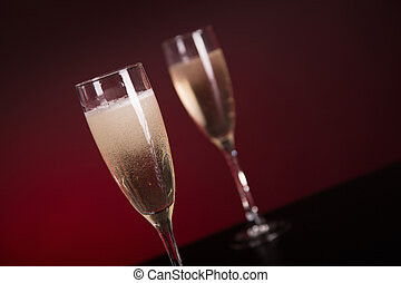 Close-up shot of two champagne glasses on glamorous red background