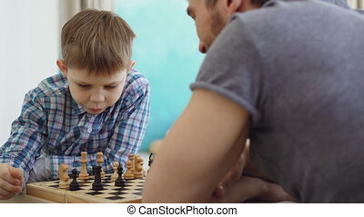 Close-up shot of two people father and son playing chess,...