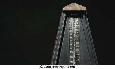 Close-up shot of vintage metronome with golden pendulum