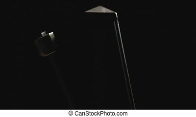 Close-up shot of vintage metronome with golden pendulum beats slow rhythm on the dark background