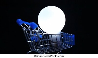 close-up shot of white electric lamp in toy shopping trolley rotating on black