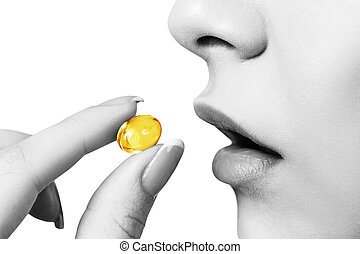 Close-up shot of woman brings the pill to her mouth.