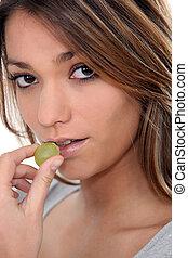 Close-up shot of woman eating grapes