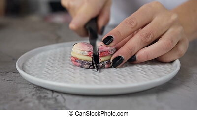 Close up shot of woman hands cutting macaroon on the halves using knife.