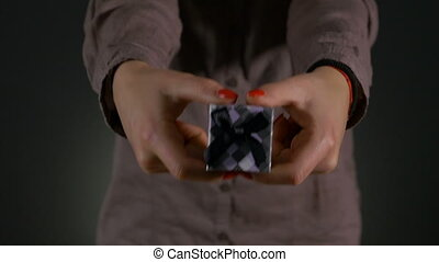 Close up shot of woman hands holding a small gift box wrapped with grey ribbon