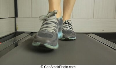 Close-up shot of Woman running on a treadmill. Sports concept