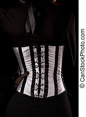 Close-up shot of woman wearing stripped black and white corset, isolated on black background