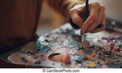 Close-up shot of woman's hand holding paintbrush and mixing...