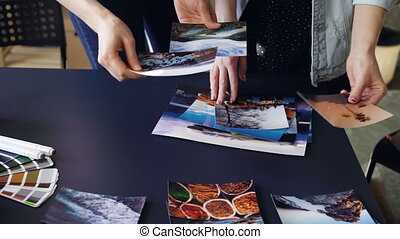 Close-up shot of women's hands placing pictures on modern...