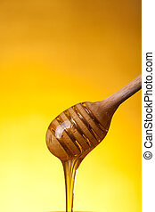 Close-up shot of wooden dipper and flowing honey
