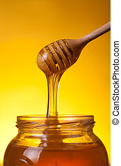 Close-up shot of wooden dipper with flowing honey
