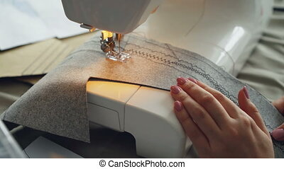 Close-up shot of working sewing machine, fabric and...