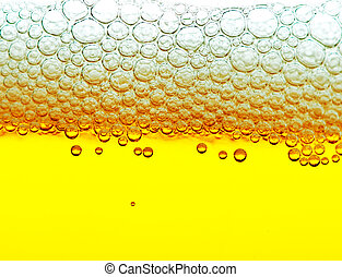 yellow beer with foam and bubbles - close up shot of yellow...