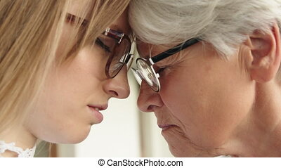 Close up shot of young and senior woman touching foreheads. High quality 4k footage