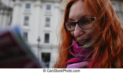 Close up shot of young beautiful attractive woman tourist with red hear and glasses uses map in center city Vienna