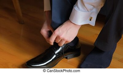 Young bridegroom is lacing the shoe. - Close-up shot of ...