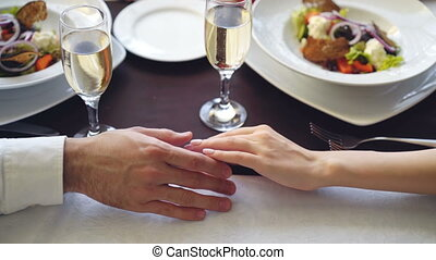 Close-up shot of young lovers touching and holding hands in classy restaurant. Table with sparkling champagne glasses, flatware and food in background.