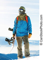 Close up shot of young snowboarder in helmet standing at the top of a mountain