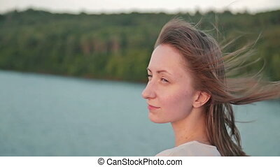 Close up shot of young woman on cruise ship at sunset