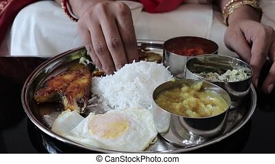 close up shot on a hand eating a non vegeterian indian thali with rice and fish and dal
